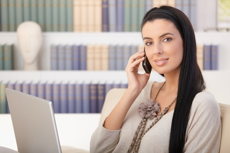 Portrait of attractive woman on mobile call sitting at home with laptop computer, smiling. photo