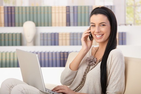Laughing pretty woman sitting on couch at home with laptop computer, speaking on mobile phone. Stock Photo - 8783240