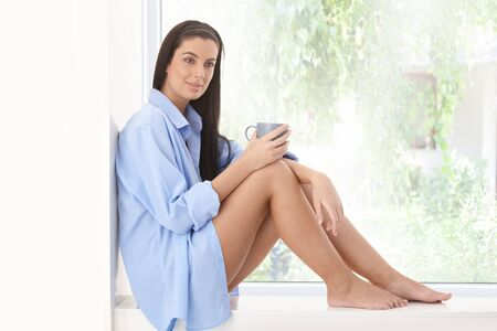 Happy woman sitting on window sill with coffee mug in morning sunshine, smiling. Stock Photo - 8782680