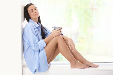 Pretty woman in shirt enjoying morning sun sitting on window sill with coffee cup handheld, eyes closed. Stock Photo - 8782676