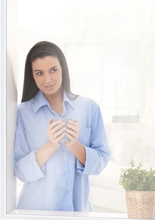 Woman looking out of home window with coffee mug handheld, smiling. photo