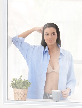 Portrait of hot woman wearing bra and shirt standing at window having coffee, looking at camera, smiling. photo