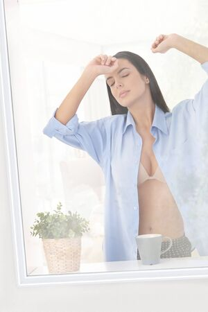 Sleepy woman wearing bra and man shirt standing at window in morning, stretching with eyes closed. photo
