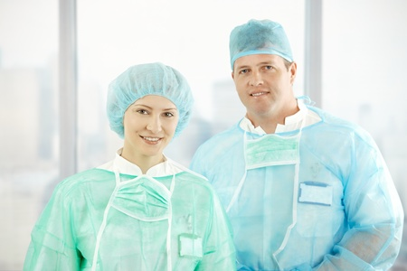 Portrait of confident surgeons smiling at camera in scrubs. photo