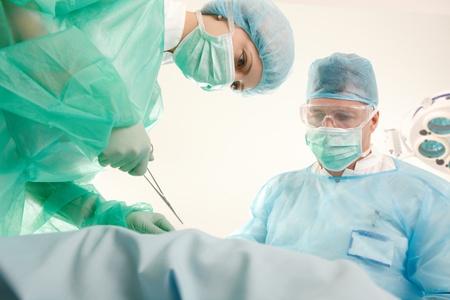 Doctors in uniform operating patient in operating theatre.