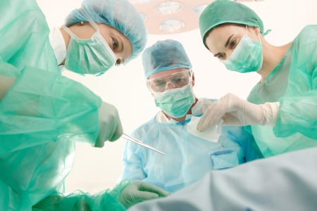 surgery doctor: Surgeons and medical assistant wearing mask and uniform operating patient. Stock Photo