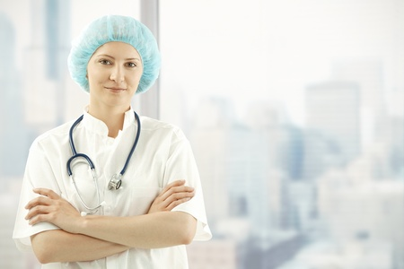smock: Mid adult female medical doctor standing in skyscraper office with arms folded, wearing white smock. Stock Photo