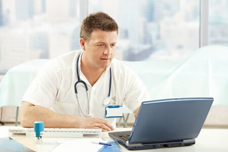 doctor computer: Mid-adult physician working with laptop in office. Stock Photo