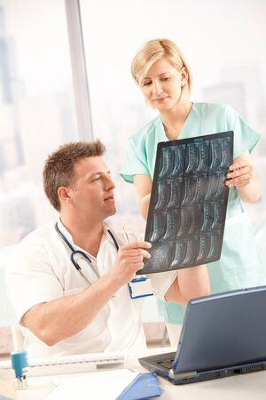 Doctor and nurse analysing x-ray image together in office. photo