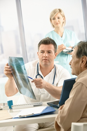 Doctor discussing diagnosis of x-ray image with older patient sitting in office, nurse in background. Stock Photo - 8783231
