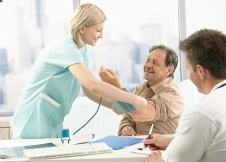 clinician: Doctor waiting for results of blood pressure measurement of senior patient, smiling nurse helping with equipment. Stock Photo