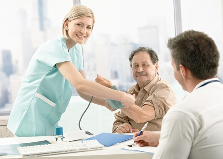 Old patient at examination in doctor's office, smiling nurse measuring blood pressure. Stock Photo - 8782902