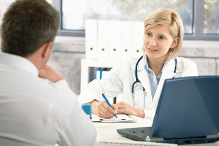patient and doctor: Doctor talking to patient in office, taking notes, smiling.