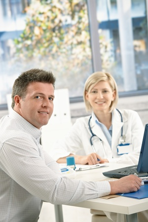 Doctor and patient sitting in office, looking at camera, smiling. photo