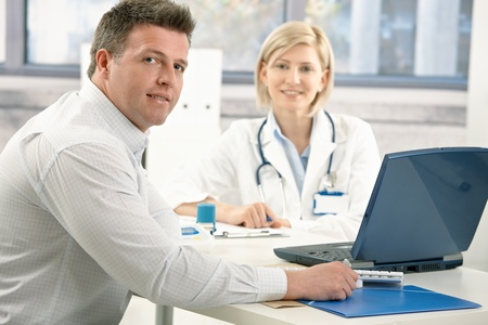 eye patient: Handsome man sitting in doctors office, smiling, on appointment with medical expert. Stock Photo