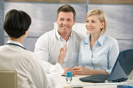 clinician: Happy couple at medical appointment, talking to doctor, smiling. Stock Photo