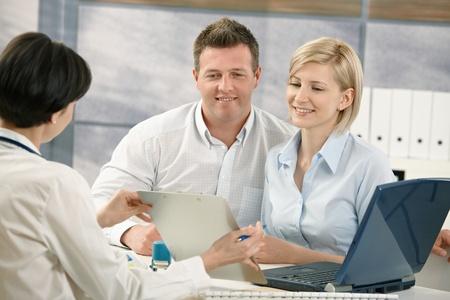 esposas: Feliz pareja hablar con el m�dico especialista, sentado en la Oficina del doctor sonriendo.