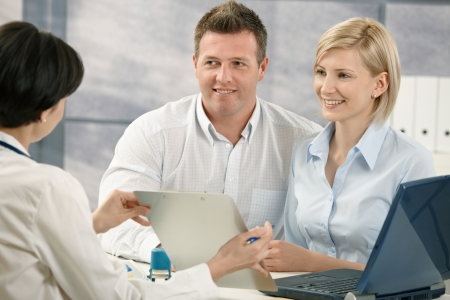 Doctor explaining medical diagnosis to smiling patients in office. photo