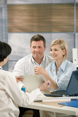 Smiling couple getting result from medical doctor in office. Stock Photo - 8783080