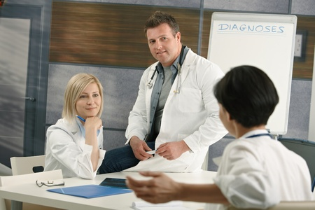clinical staff: Medical doctors discussing diagnosis sitting in doctors room.