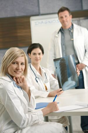 Portrait of medical doctors consulting about x-ray image, looking at camera, smiling. photo