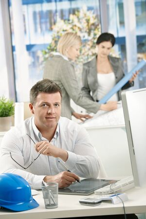 Portrait of designer at work, using drawing pad, with coworkers working in background. Stock Photo - 8783193