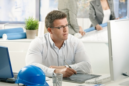 Concentrating architect at work, sitting at desk using drawing pad. Stock Photo - 8783191