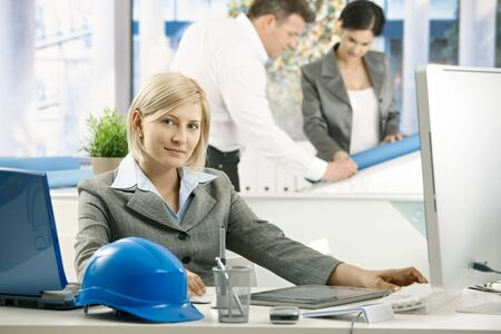 Portrait of architect sitting in office, smiling, coworkers working in background. photo