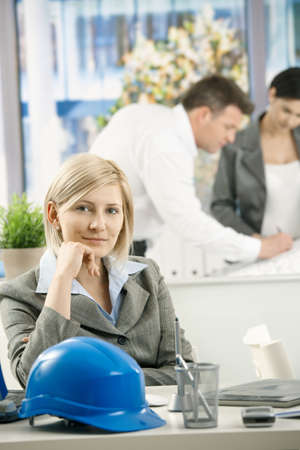 office wear: Smiling designer sitting at desk, other architects working in background. Stock Photo