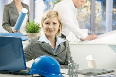 Portrait of mid-adult designer in architect office, smiling at camera, photo