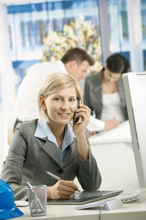 Portrait of smiling female professional sitting in designer office, talking on phone. photo