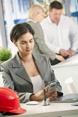 Businesswoman sitting in architectural office using smartphone. photo
