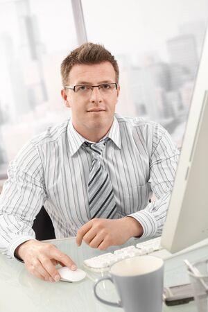 Portrait of businessman using desktop computer, looking at camera. photo