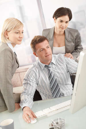 Businessteam at work, looking at computer screen in office. Stock Photo - 8783370