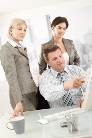 Businesspeople at work, businessman pointing at computer screen, coworkers watching. Stock Photo - 8783373