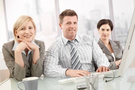 Portrait of confident business team sitting at table, smiling at camera. photo