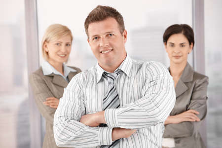Smiling businesspeople portrait, standing in office, looking at camera with arms folded. Stock Photo - 8783196