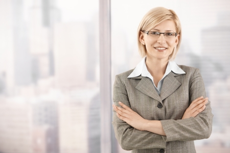 30s adult: Portrait of smiling mid-adult businesswoman standing at skyscraper window.