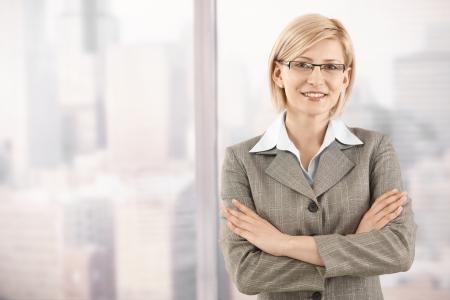 businesswoman suit: Retrato de sonriente empresaria mid-adult permanente en la ventana de rascacielos.