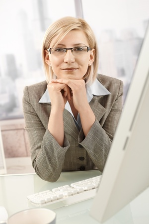 Confident businesswoman sitting at desk, smiling at camera. photo