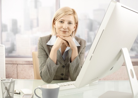 Portrait of mid-adult smiling businesswoman sitting at office desk. photo