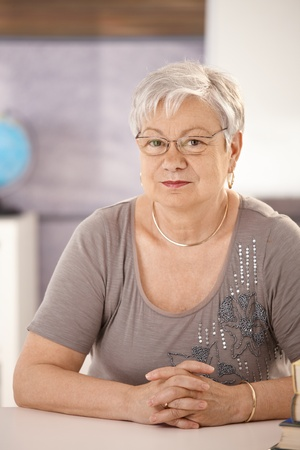 only mature women: Portrait of senior teacher in classroom, looking at camera.