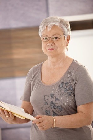 older person: Portrait of senior teacher standing in classroom, holding textbook, looking at camera.
