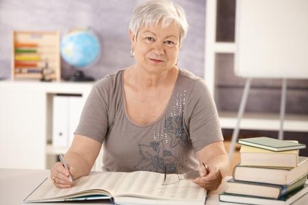 Retrato de profesor senior trabajando en escritorio en el aula, mirando la cámara.