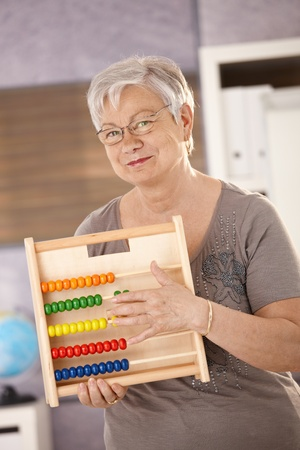 Senior teacher standing in classroom, holding abacus, smiling. Stock Photo - 8783749