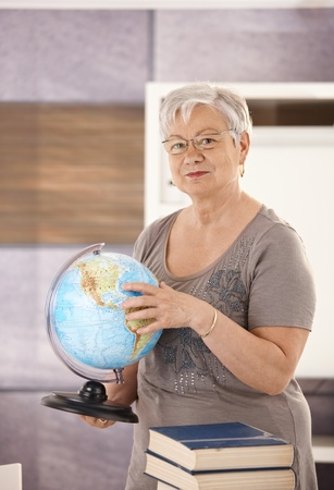 Senior teacher standing at desk, holding globe, teaching geography in elementary school. photo