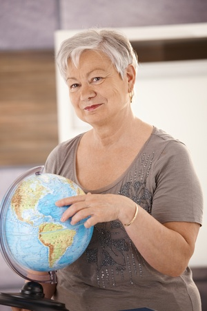 Senior teacher standing at desk, pointing at globe, teaching geography in elementary school. photo