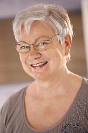woman wearing glasses: Closeup portrait of happy senior woman wearing glasses, looking at camera, smiling. Stock Photo