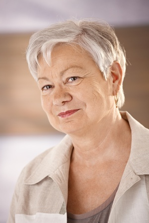 Closeup portrait of female pensioner with white hair, looking at camera, smiling. photo
