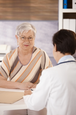 Female pensioner at doctors office looking at camera. photo